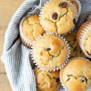 a close up of Low Carb Chocolate Chip Muffins in a bowl with a striped towel.