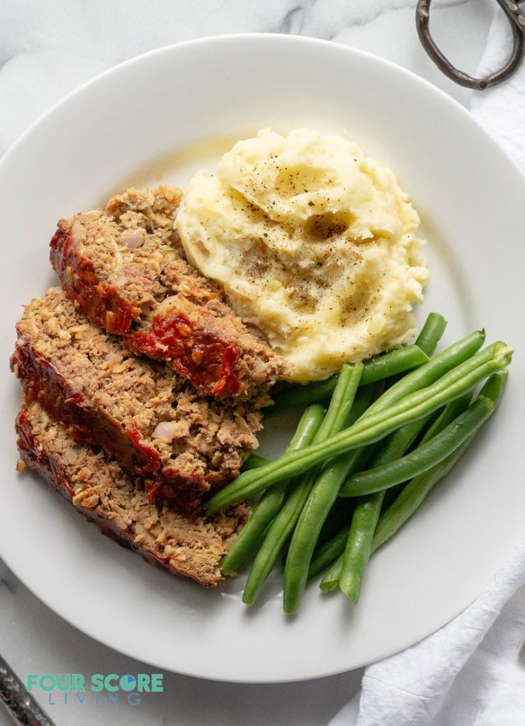 a top down view of Sliced low carb meatloaf on a white plate with greens and mashed cauliflower