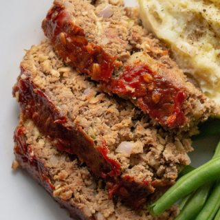 a close up of Sliced low carb meatloaf on a white plate with greens and mashed cauliflower