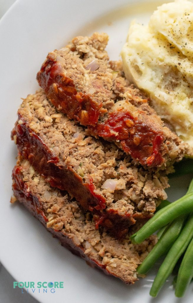 Sliced low carb meatloaf on a white plate with greens and mashed cauliflower