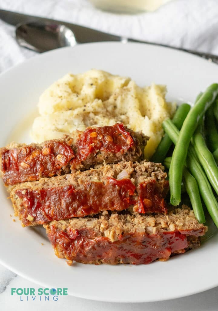 a side view of Sliced low carb meatloaf on a white plate with greens and mashed cauliflower