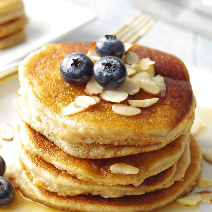 a close up of Stack of low carb pancakes topped with blueberries and sliced almonds