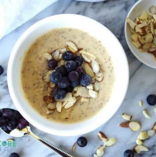 a close up of Low Carb Oatmeal in a white bowl with blueberries next to a spoon