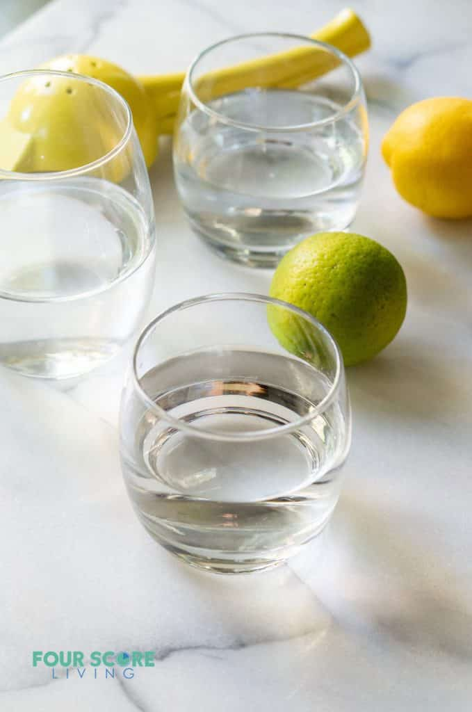 a glass on water in front of another glass of water and a lemon and lime