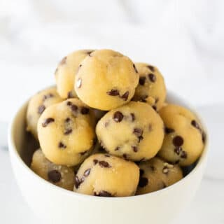 a close up of keto cookie dough bites in a white bowl
