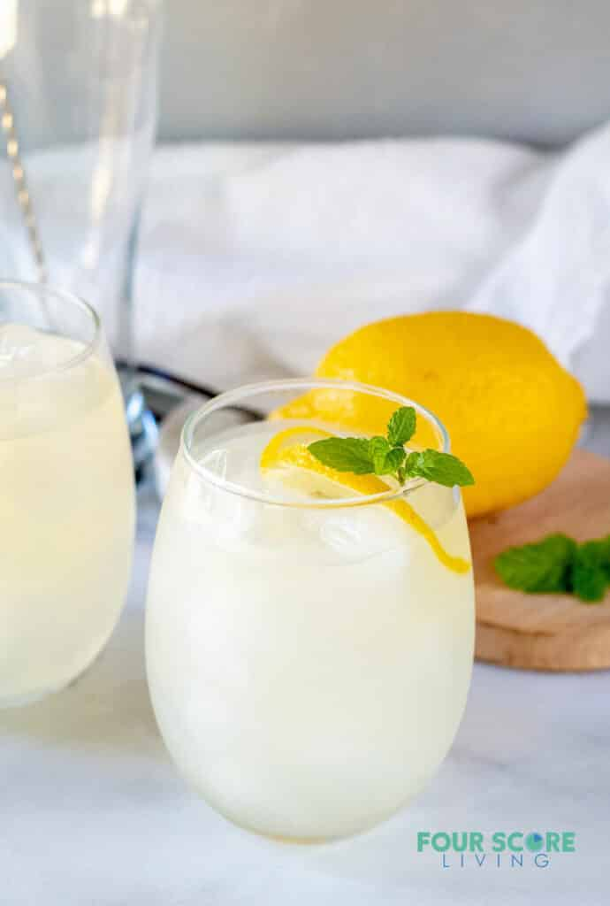 keto lemonade in a glass with lemon and mint with a lemon in the background