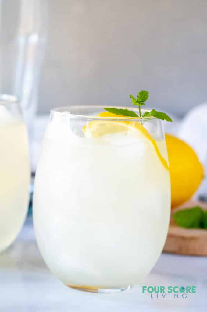 a close up of keto lemonade in a glass with lemon and mint
