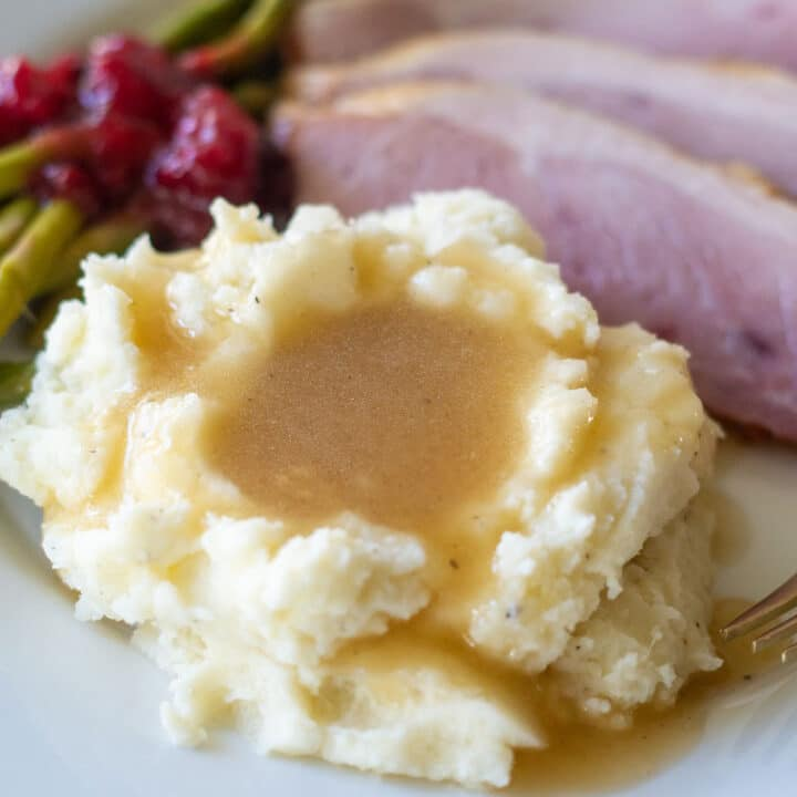 keto gravy over mashed cauliflower on a plate with ham