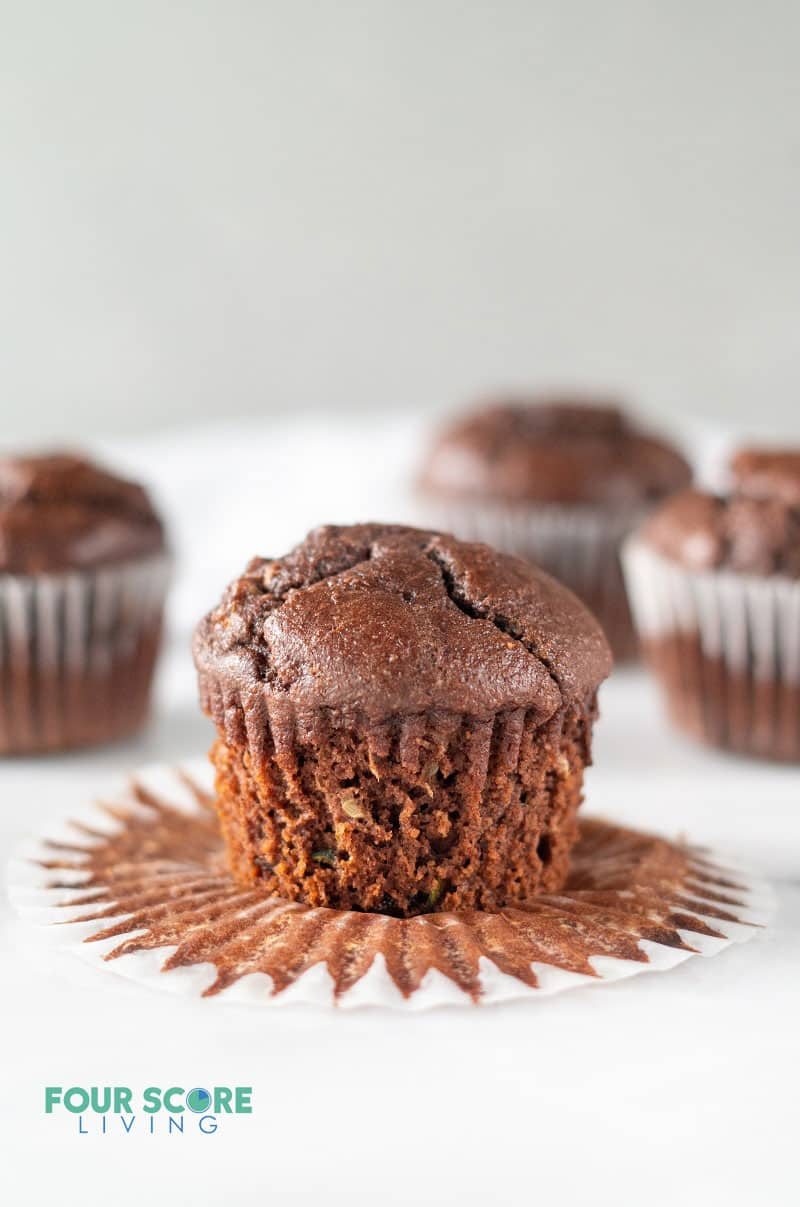 a chocolate muffin sitting on an open cupcake wrapper with several more chocolate muffins in the background