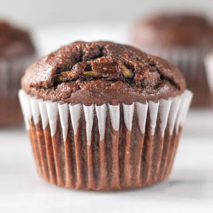 close up of a chocolate zuchinni muffin in a white cupcake liner