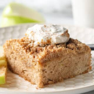 a square of keto coffee cake with streusel and whipped cream on top