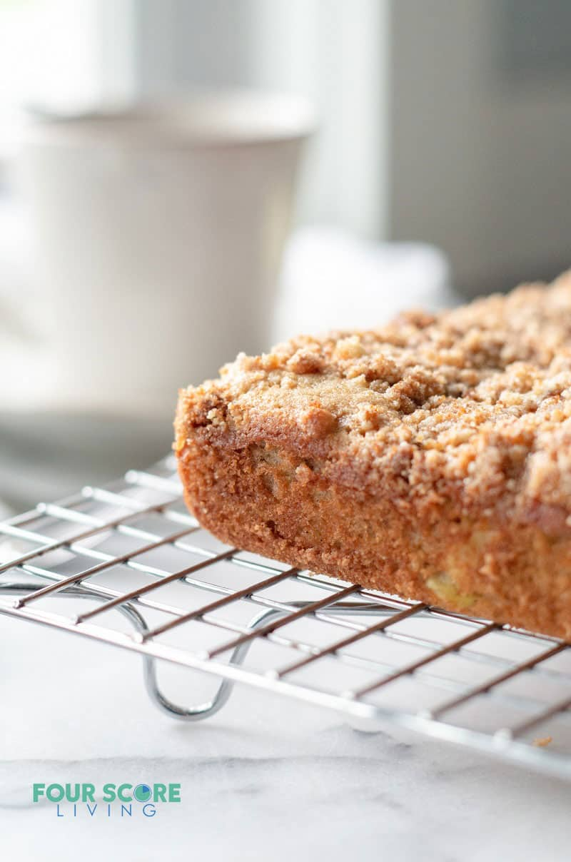 a coffee cake with streusel topping cooling on a wire rack