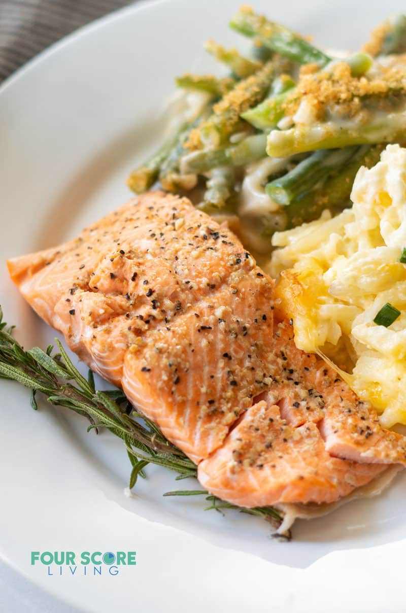 a salmon filet on a plate with cheesy cauliflower and green beans