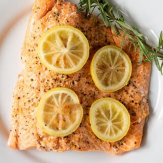 a cooked fillet of salmon topped with lemon slices and a sprig of fresh herbs
