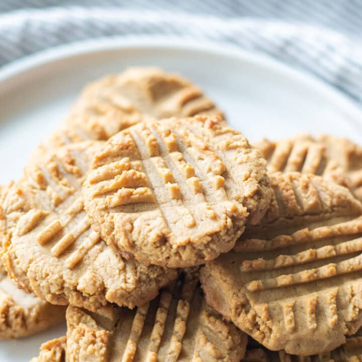 a pile of peanut butter cookies on a round white plate