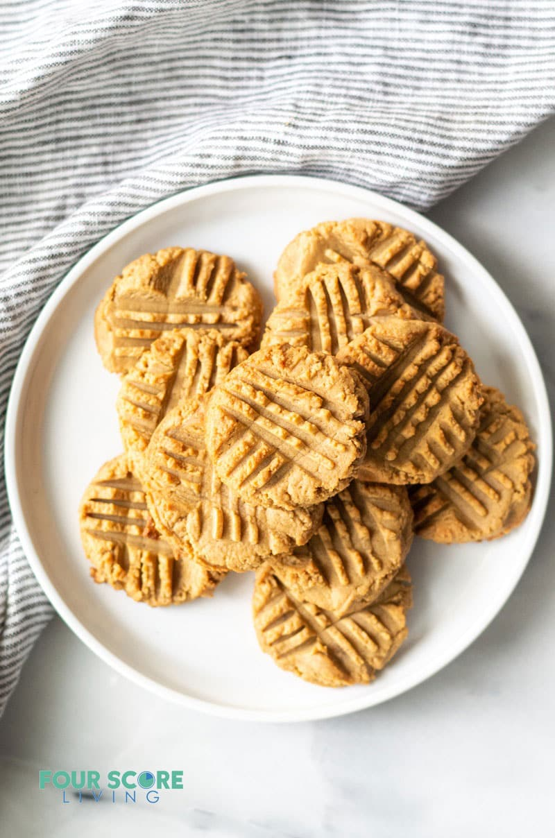 a stack of keto peanut butter cookies on a round white plate over a gray dish towel