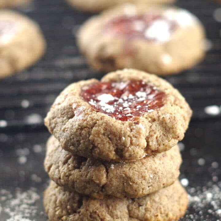 a stack of round thumbprint cookies with strawberry jam and powdered sugar