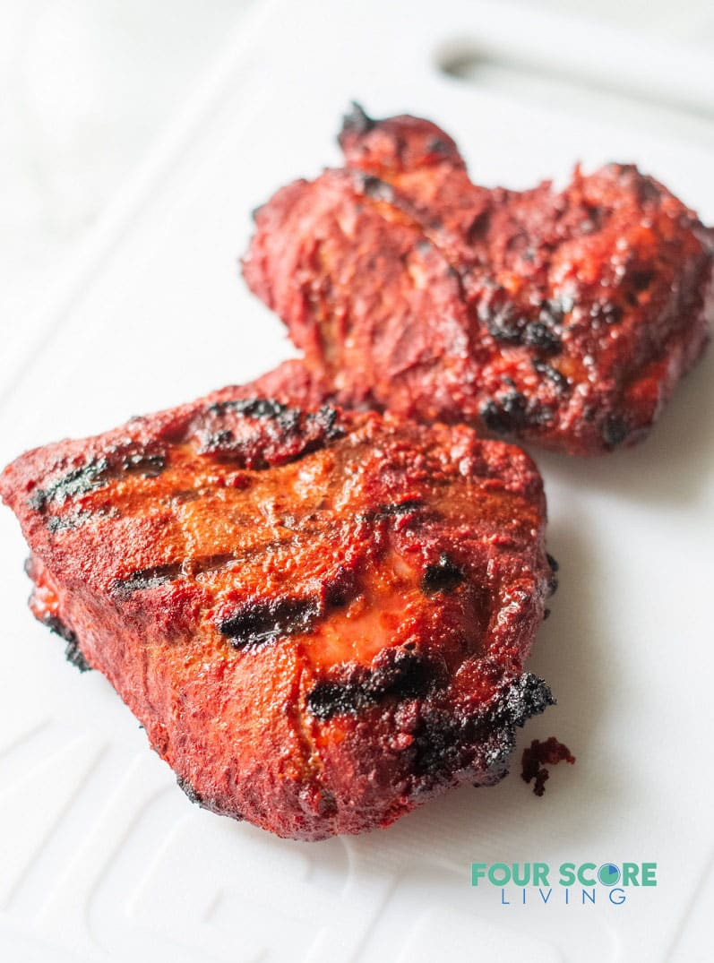 filets of cooked spiced pork with red-colored seasoning and black grill marks on a white cutting board