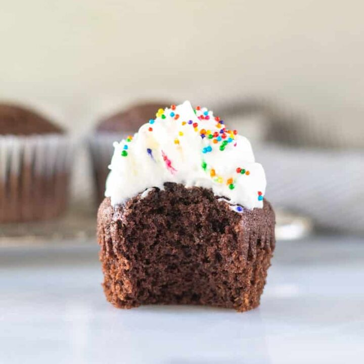 a keto chocolate cupcake with a bite out with whipped cream and sprinkles on top