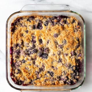 a clear square pan filled with a browned cake studded with blueberries