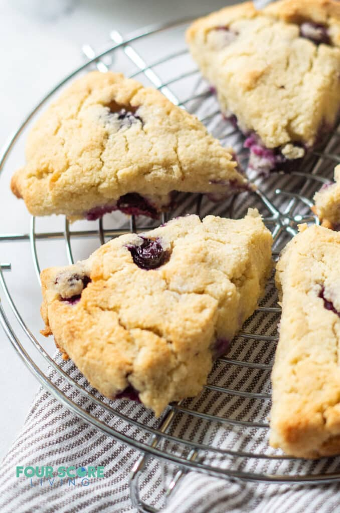 a side view of keto blueberry scones on a wire cooling rack showing the texture