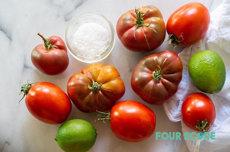a variety of tomatoes with a bowl of salt and two limes