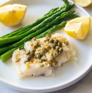 Cod topped with capers and garlic served with lemon wedges and asparagus on a white plate.