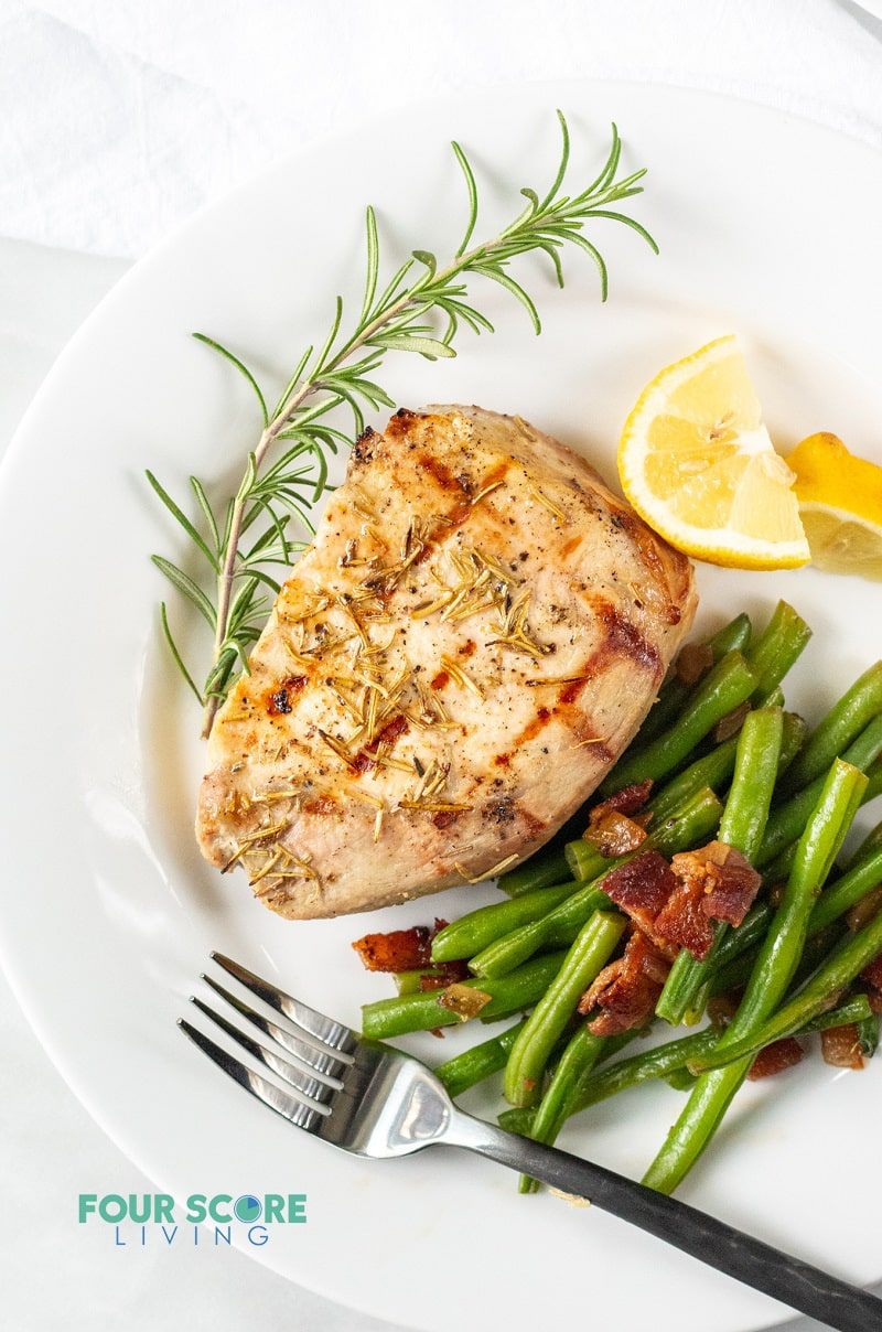 pork chop on a plate served with green beans, lemon wedges, and a rosemary garnish.
