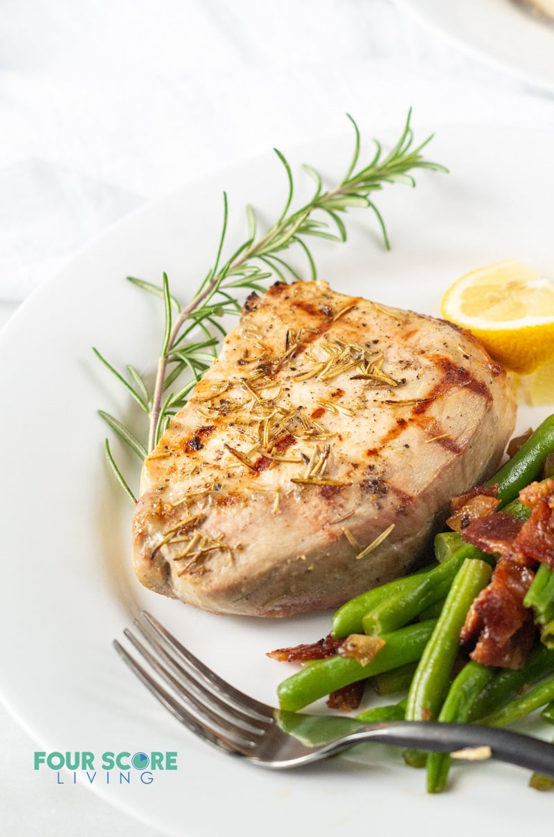 closeup of grilled pork chop on a plate, served with green beans with bacon, garnished with rosemary