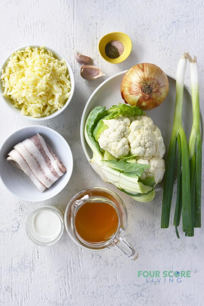 Ingredients for cauliflower soup in separate bowls, including bacon, cauliflower, cheese, onion, and seasonings.