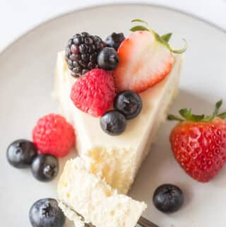 a slice of cheesecake on a plate, topped with fresh berries with a bite being taken.