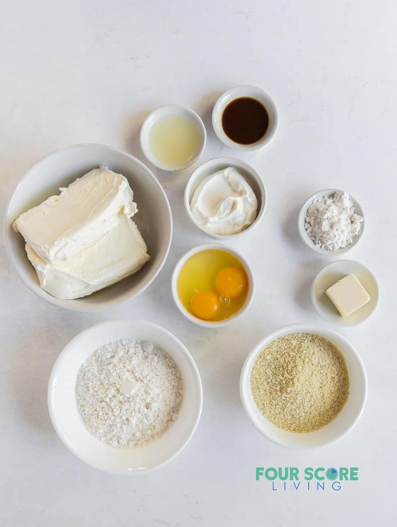 ingredients for cheesecake, in small bowls on a counter