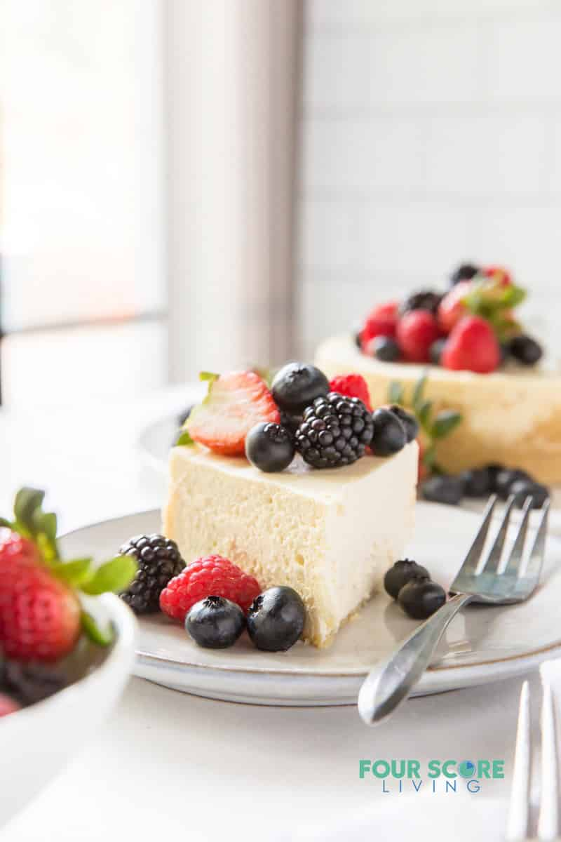a slice of cheesecake topped with fresh berries. the rest of the cheesecake is in the background.