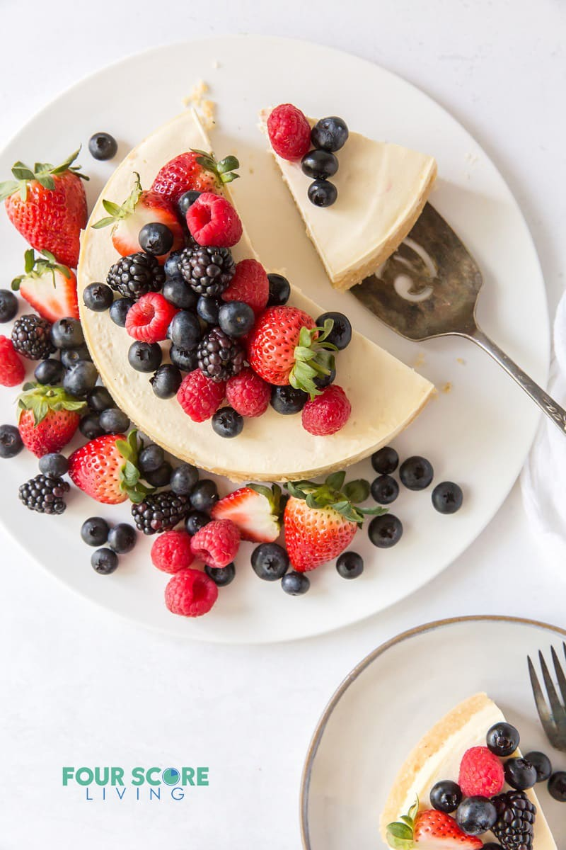 top down view of cheesecake topped with fresh berries. One slice is on a plate, another slice is being served.