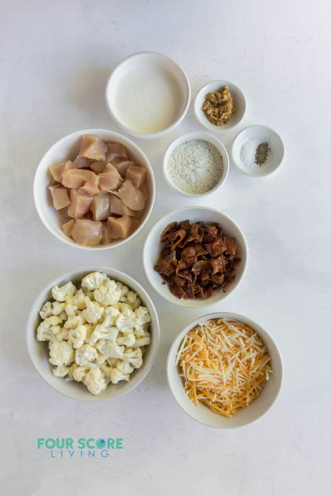 Top down image of small bowls with casserole ingredients, including chicken, cauliflower, cheese, bacon, and seasonings.