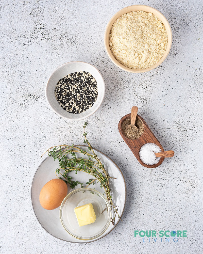 ingredients for keto crackers in separate dishes, including flour, seeds, egg, butter, and seasonings