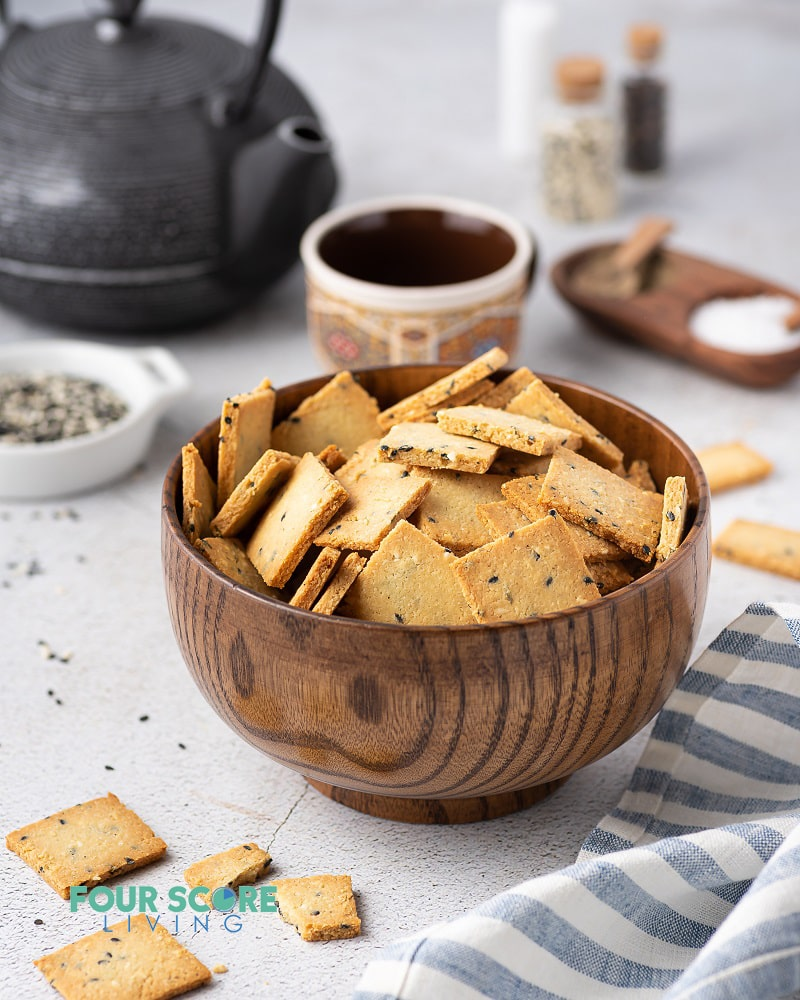 a wooden bowl full of square crackers being served with tea.