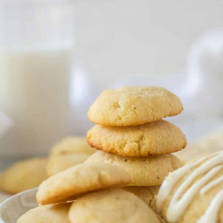 a stack of cream cheese cookies on a plate next to a glass of milk.