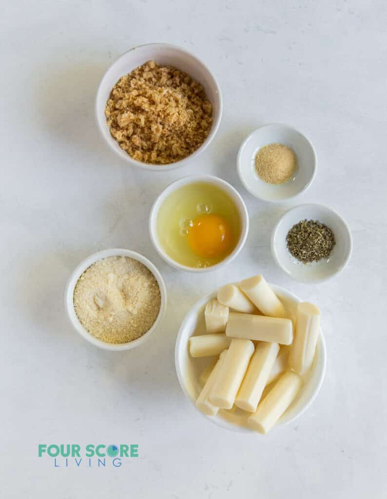 Ingredients for making keto mozzarella sticks, each in separate bowls. Including cheese sticks, pork rinds, egg, and seasoning.