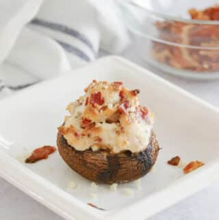 A cheesy stuffed mushroom with bacon on a small square plate.