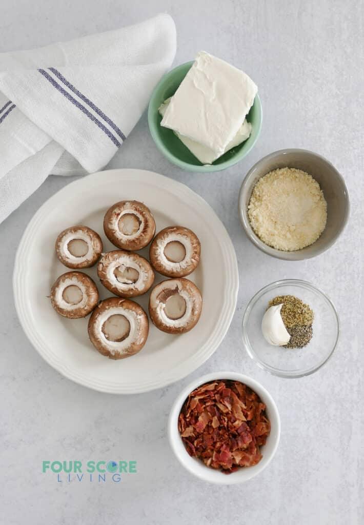 Top down view of ingredients for stuffed mushrooms, including mushroom caps, bacon, cheese, and seasonings.