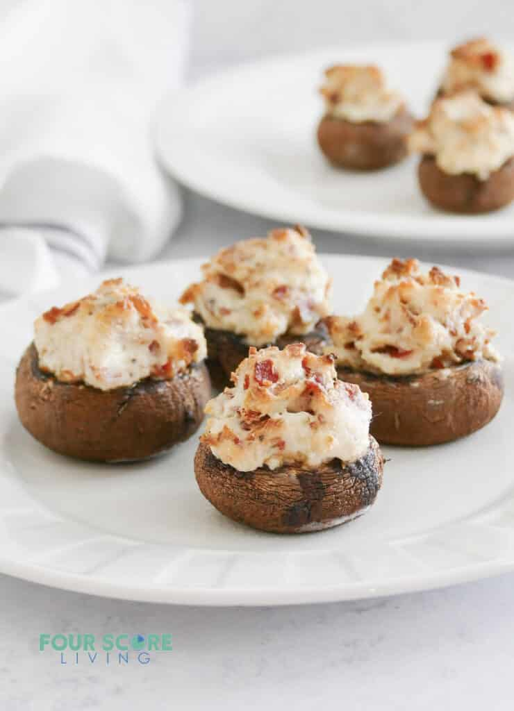 A round white plate of stuffed mushrooms filled with bacon and cheese.