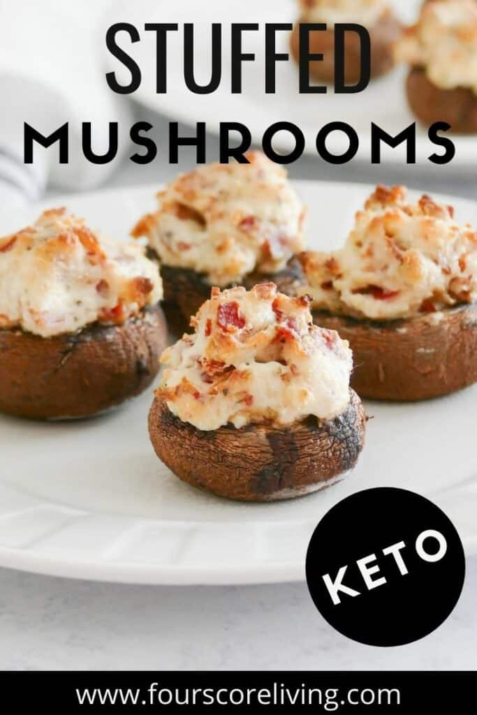 A round white plate of stuffed mushrooms filled with bacon and cheese, with the title, Stuffed Musrooms, Keto.