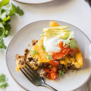 a slice of taco pie on a plate, topped with sour cream, avocoado, tomatoes, and cilantro.