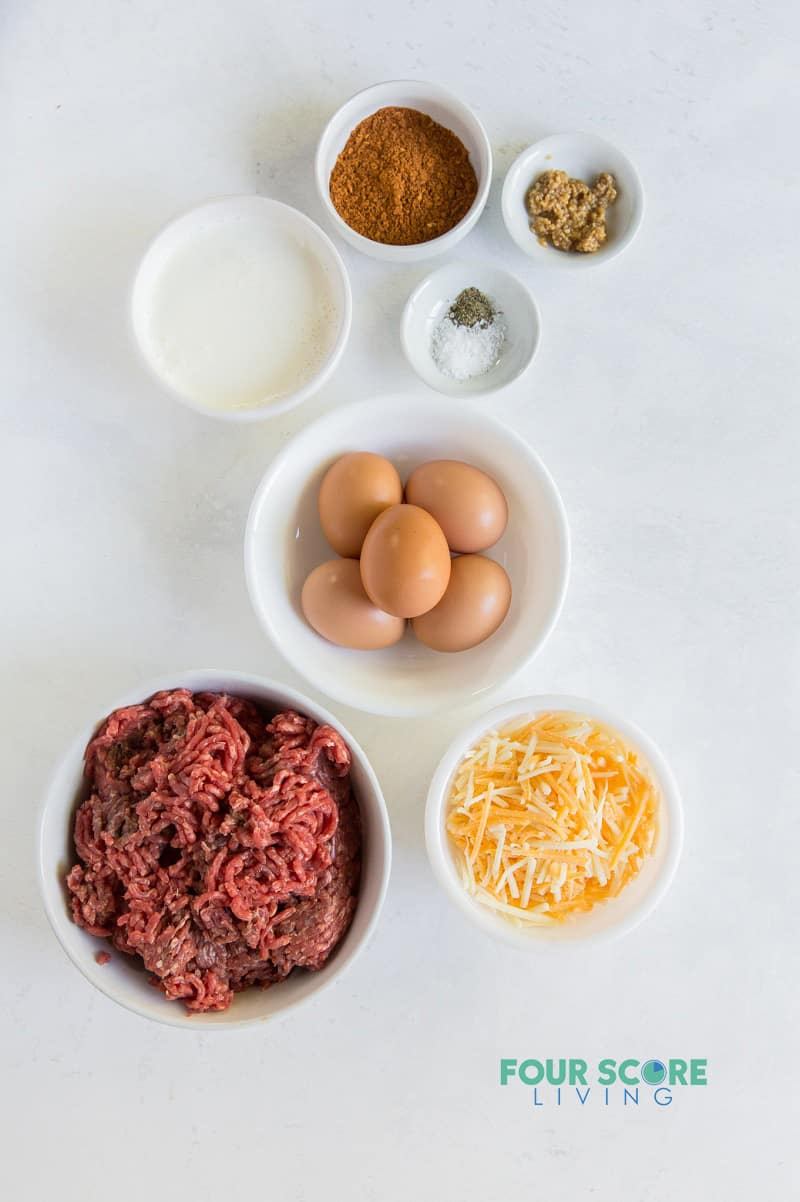 top down image of ingredients for taco pie, including ground meat, cheese, eggs, and seasonings.