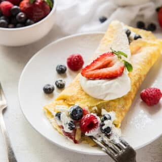 a round white plate with a folded crepe stuffed with cream and mixted berries, being eated with a fork.. Near the plate is a bowl of berries and a bowl of whipped cream