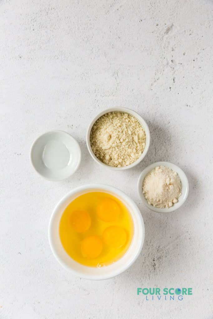 4 small bowls with the ingredients needed for crepes including flour, sweetener, and eggs.
