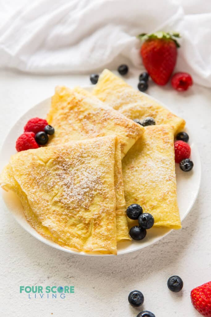 a round white plate topped with crepes folded in triangles topped with raspberries and blueberries