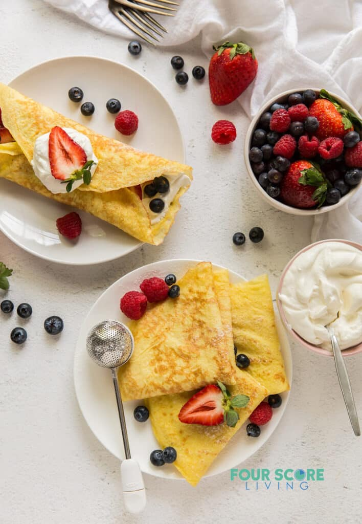 top down view of a countertop with one filled crepe on a plate, one plate of folded crepes, a bowl of berries, a bowl of whipped cream, and servingware