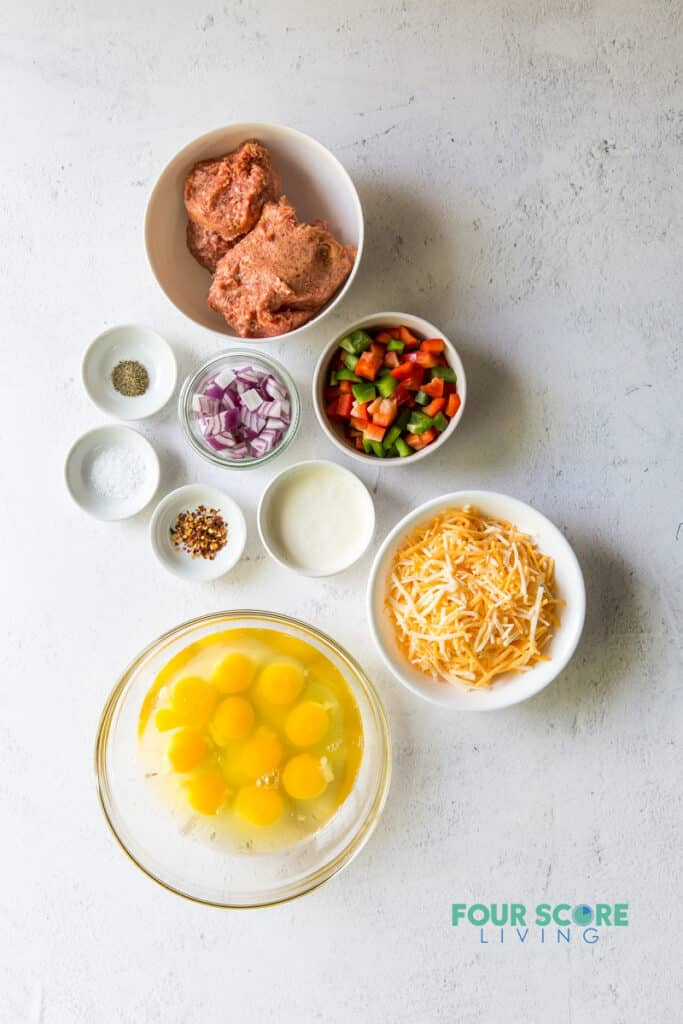 Top down view of ingredients to make breakfast casserole in separate bowls, including sausage, eggs, vegetables, cheese, and seasonings.